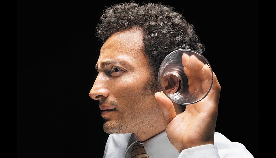 Hombre utilizando un vaso para escuchar