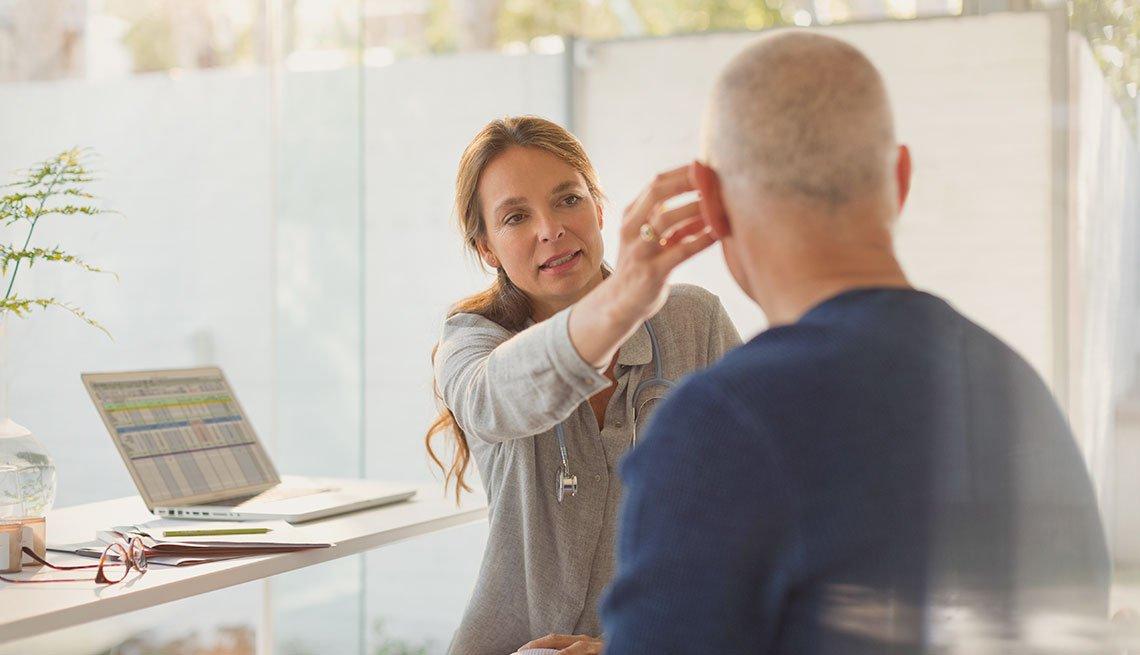 Mujer ajusta aparato auditivo de un hombre mayor.
