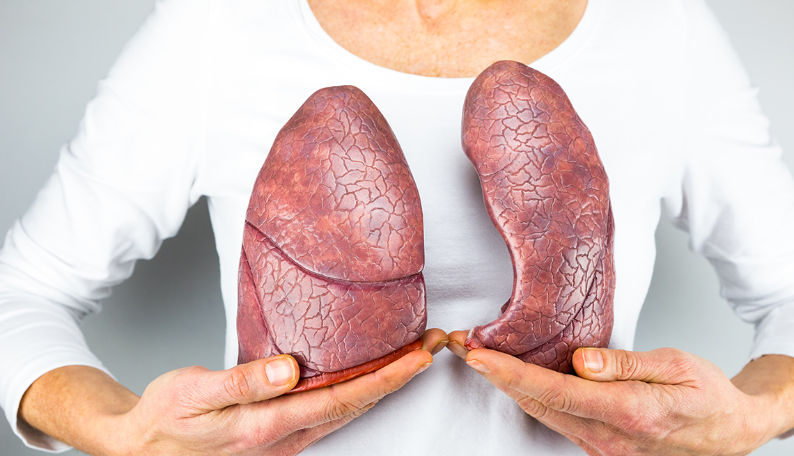 Woman holding models of lungs