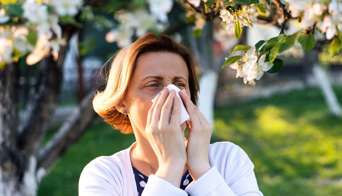 a mature woman sneezing