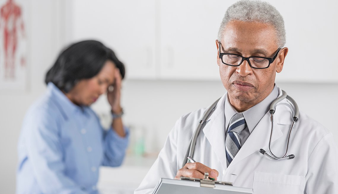 Doctor prescribing medication to a woman with a headache or migraine