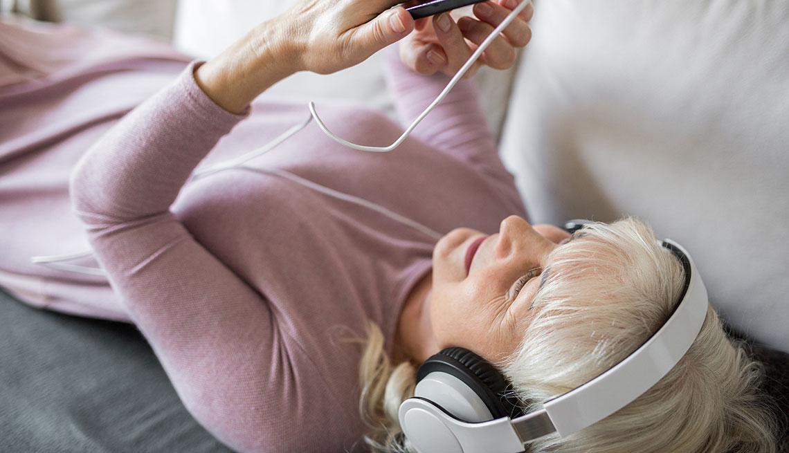 Glad senior lady lying on couch listening music on mobile