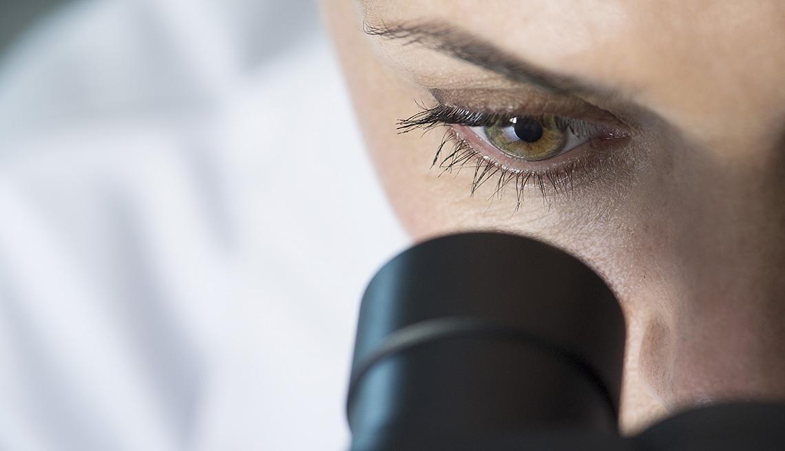 Médico mirando por el visor de un microscopio