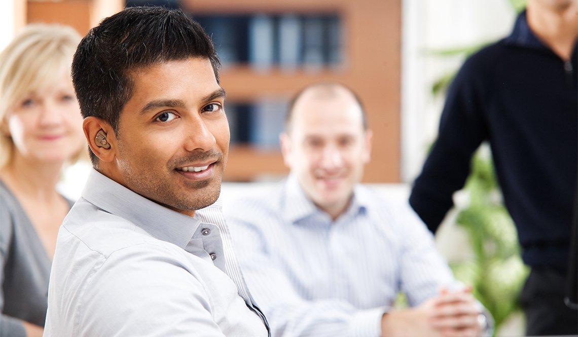 Hombre con audífonos en una reunión de trabajo