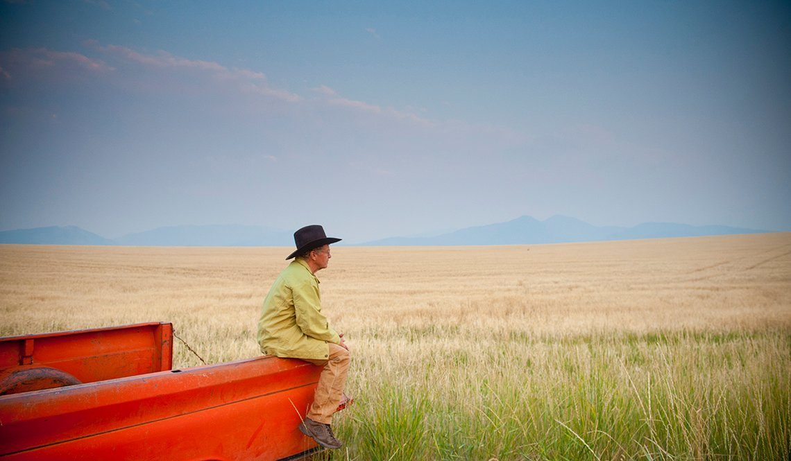 Farmer in brown hat sits on the edge of his red pickup truck in a wheat field.