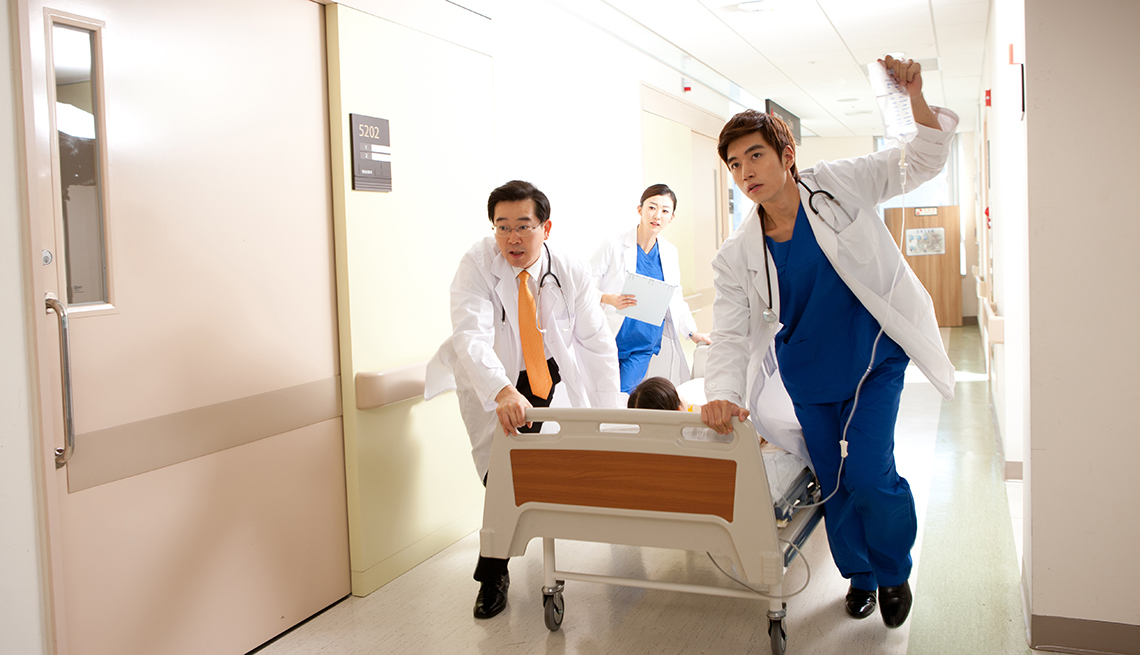 Three doctors rushing a patient on a gurney through the hospital.