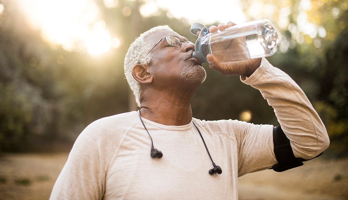 A man drinking water outdoors