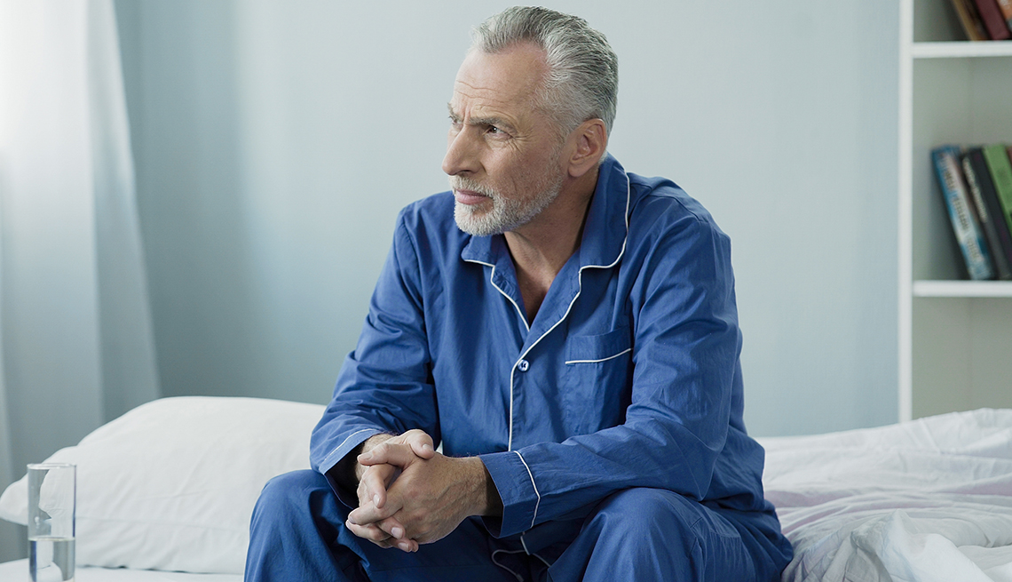 Man sitting on bed appearing upset.