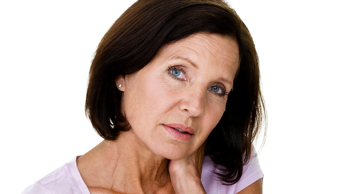 Mature woman in pink shirt touching her neck looking concerned or uncomfortable.