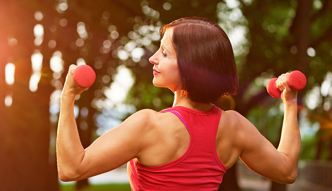 Mature woman working out with small dumbbells in the park in the morning.