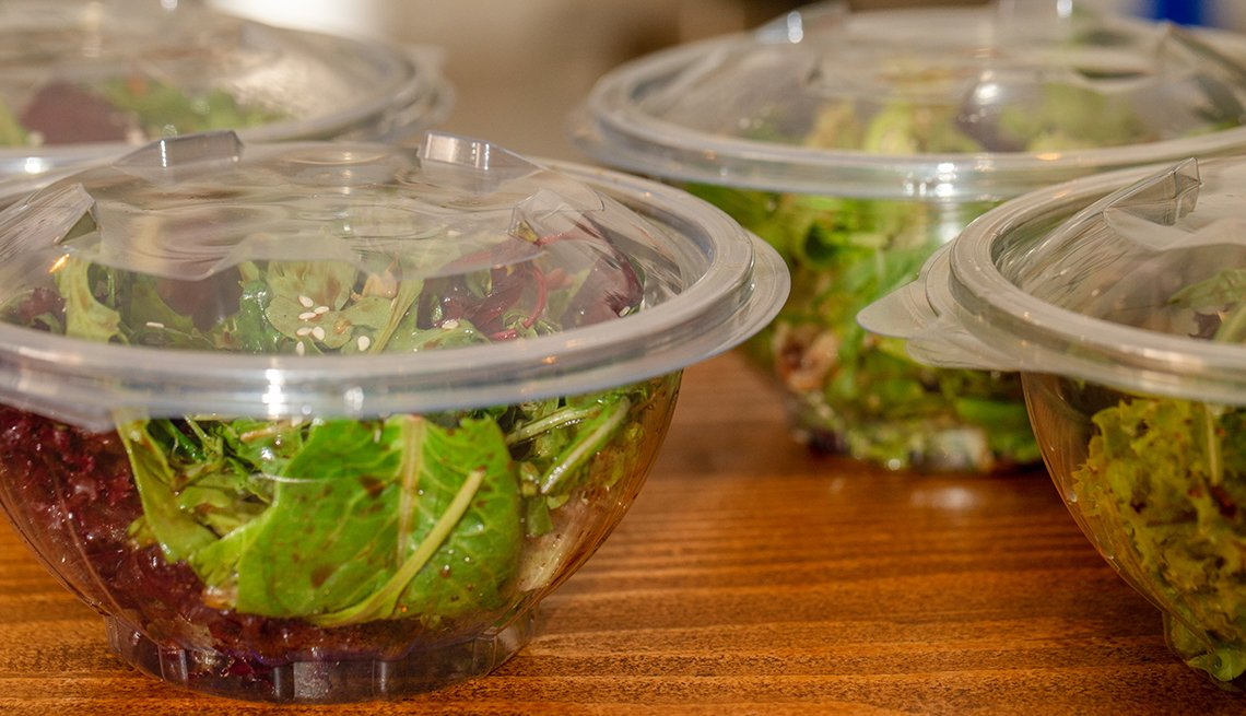 Green salad mix inside transparent take away bowl packages. Baby spinach, arugula, lettuce, rocket, romaine in disposable plastic packaging.
