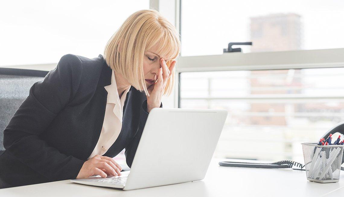 Mujer frente a su computador sintiéndose mal
