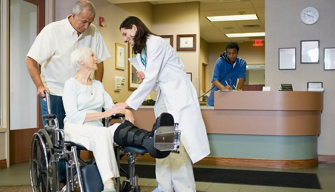 Mature woman sitting in wheel cheer, has a broken leg propped up. She is talking to a doctor in a hospital. Mature man is holding the wheelchair behind her.