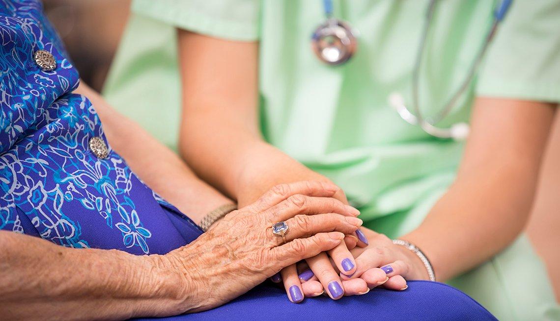 Personal médico sosteniendo las manos de una mujer mayor