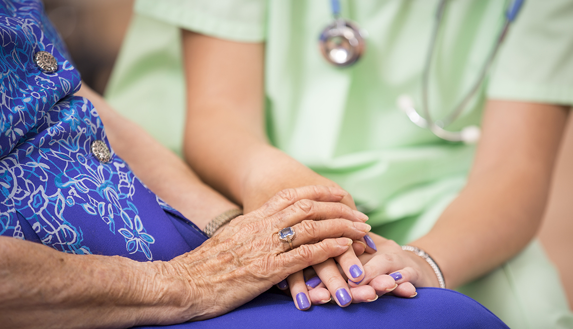 Close-up of older female patient in nursing home holding hands with her nurse.
