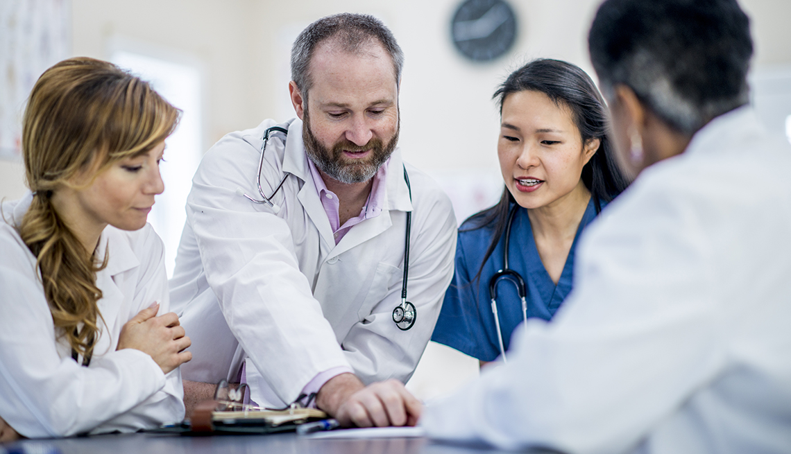 Doctors at a table discussing a patient's care plan