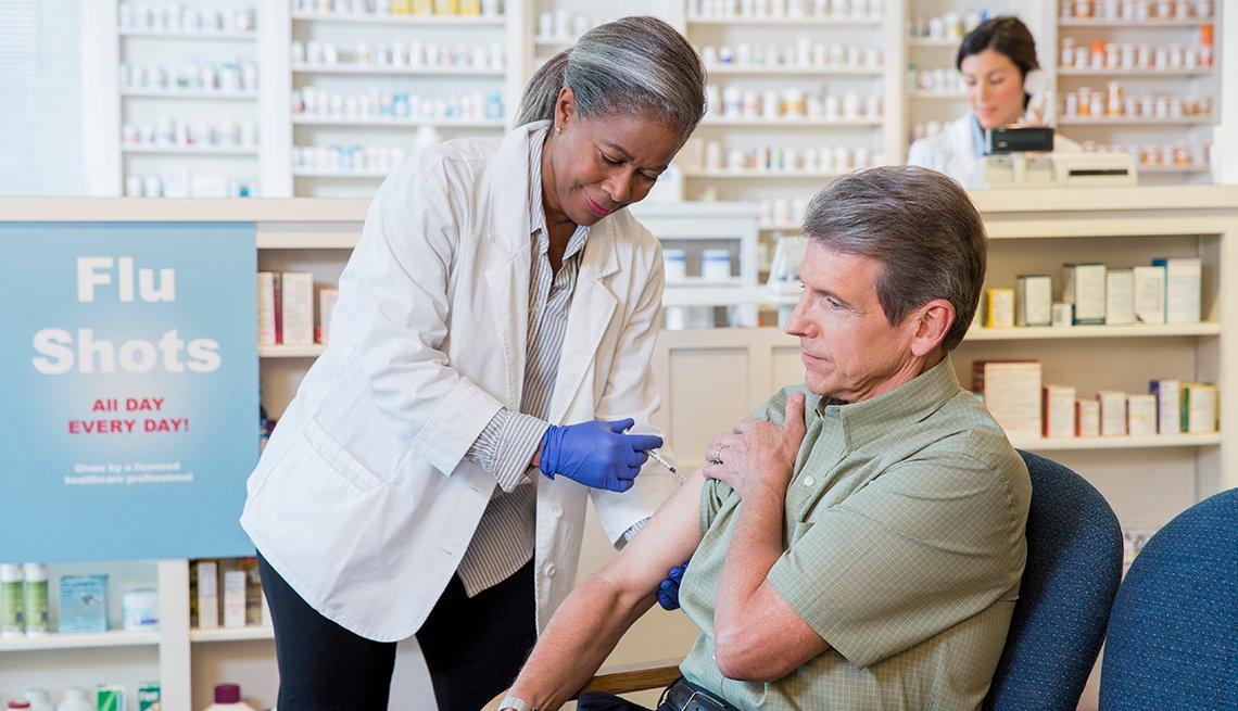 Hombre recibiendo su vacuna en una farmacia