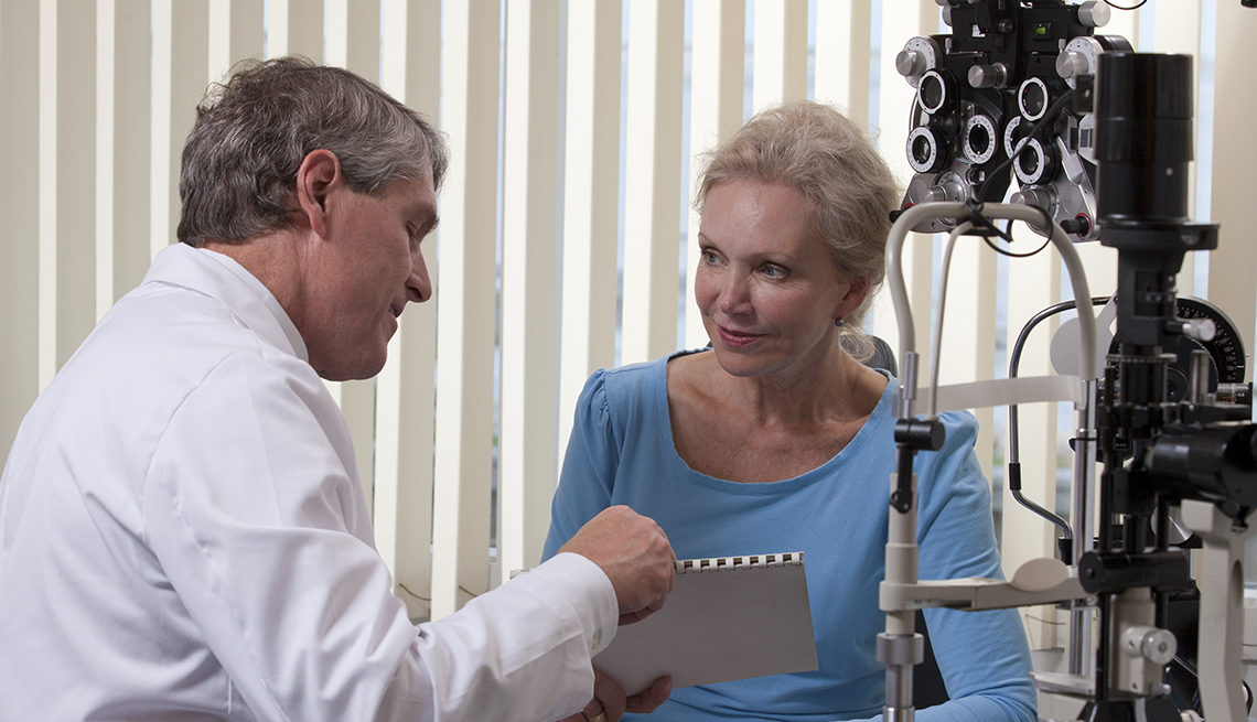 Ophthalmologist counseling mature patient regarding her eye condition.