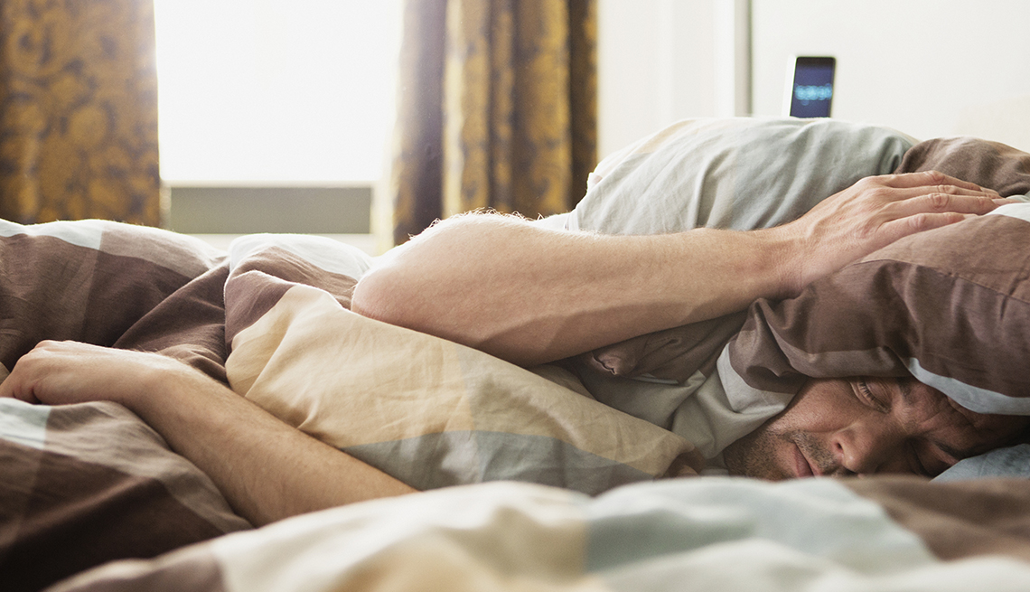 Man lying down in bed, trying to avoid waking up by covering his head with the pillow to block the sunlight.