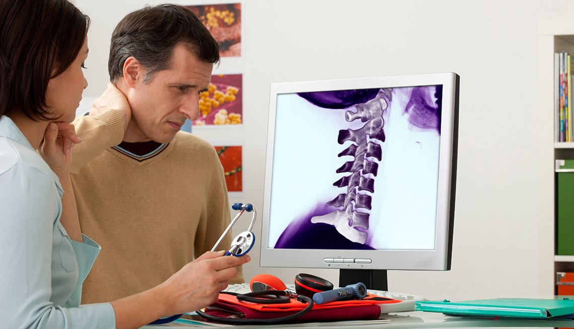 A mature man getting an orthopedics consultation. The computer screen shows an xray of his neck.