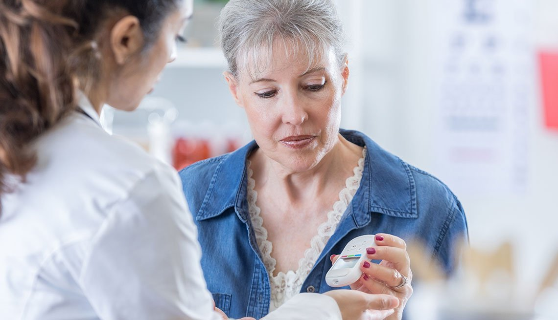 Mujer midiendo su nivel de azúcar con ayuda de un profesional