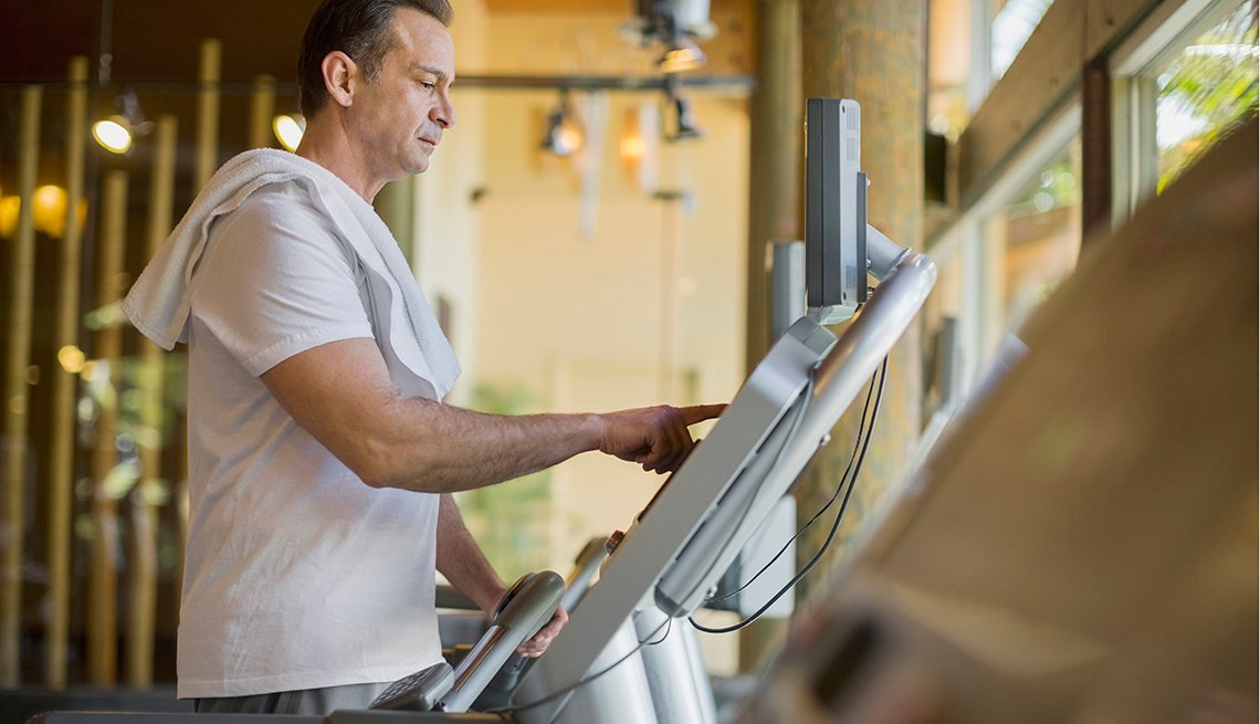 Mature man looking serious, changing the settings on a treadmill.