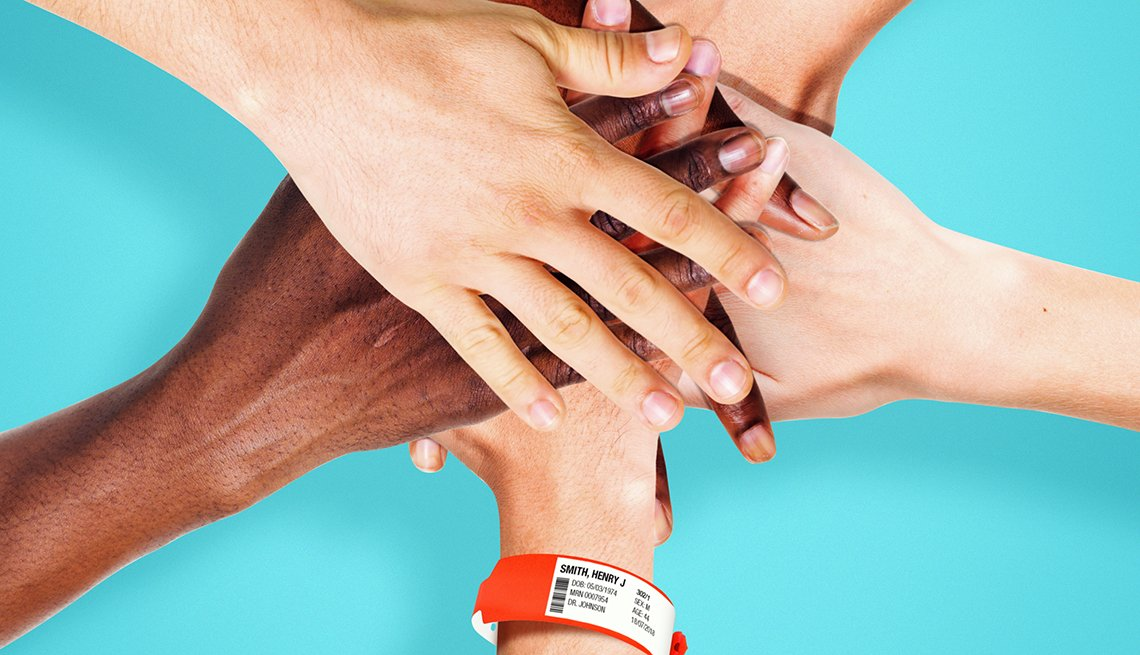 A  group of hands on top of one another symbolizing a team. The bottom hand had a patient wrist band attached.