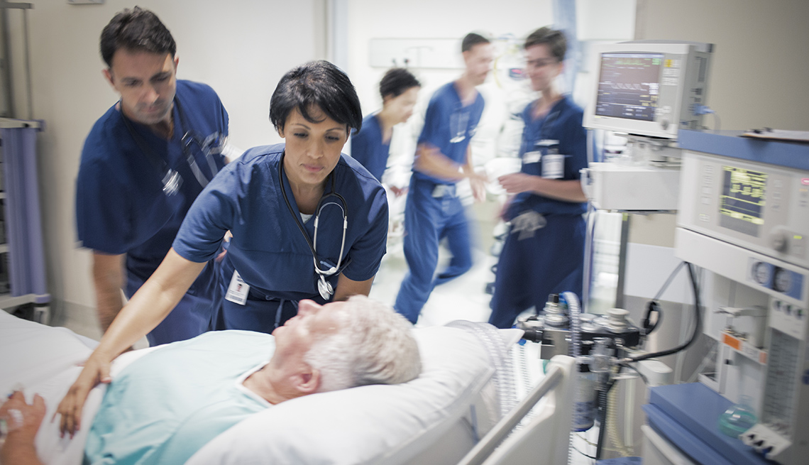 Mature man in hospital bed, doctors and nurses rushing around him.