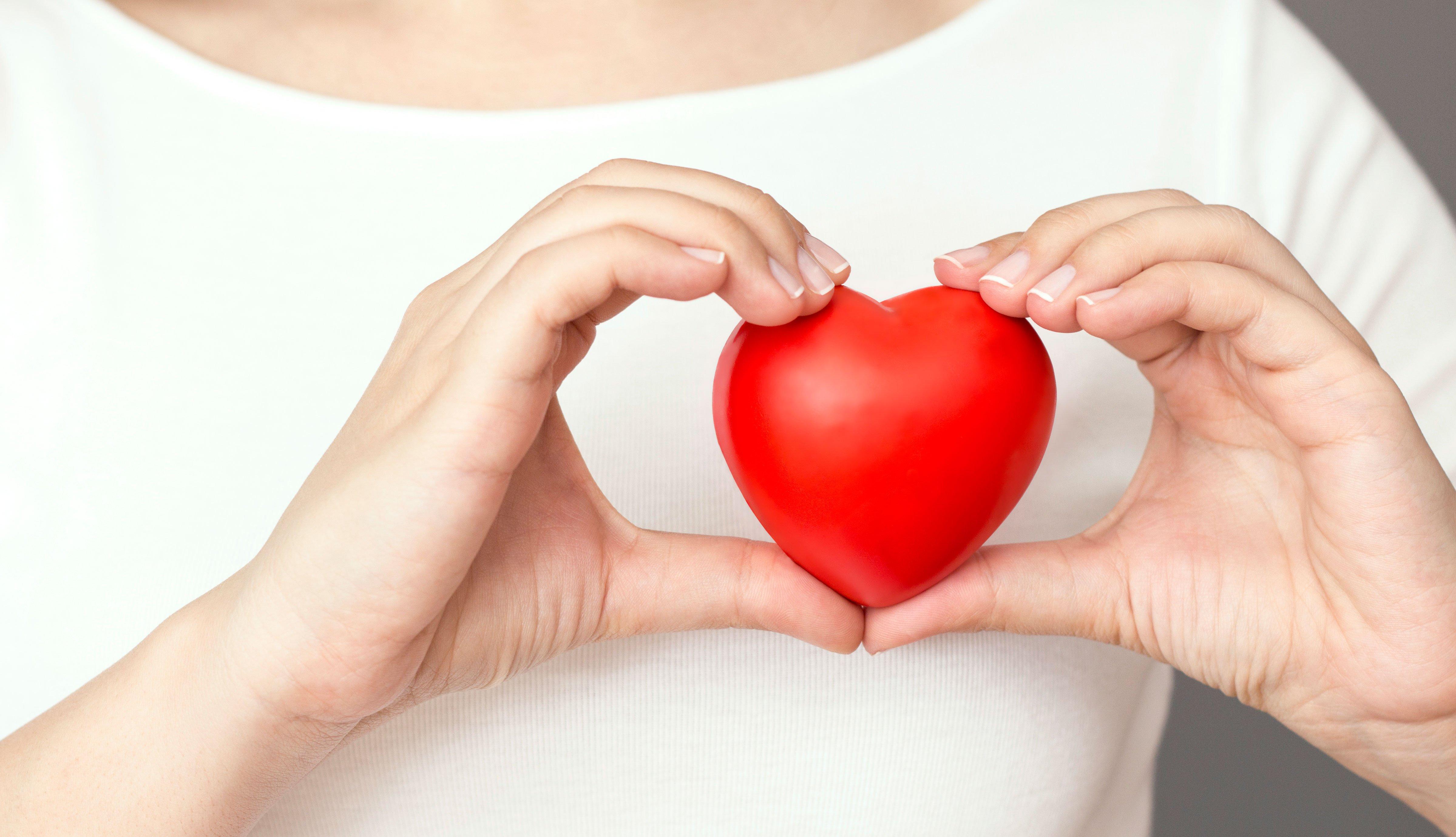 Mujer sostiene un corazón de plástico
