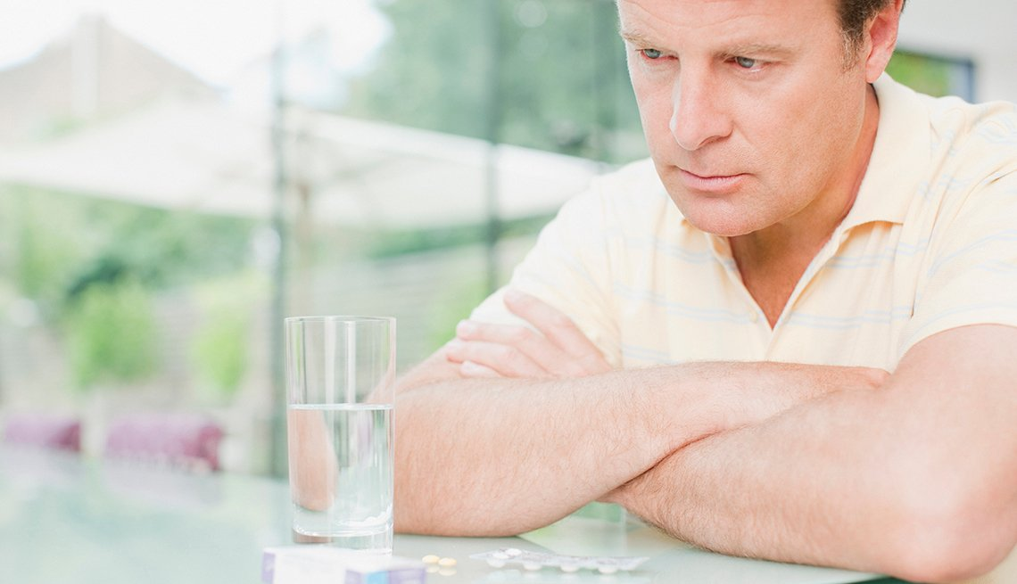 Worried man staring at glass of water with pills scattered on the table