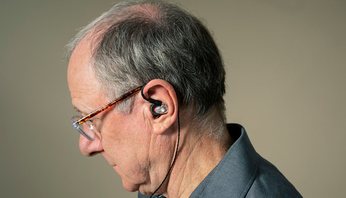 A person with headphones in his ear to help treat tinnitus