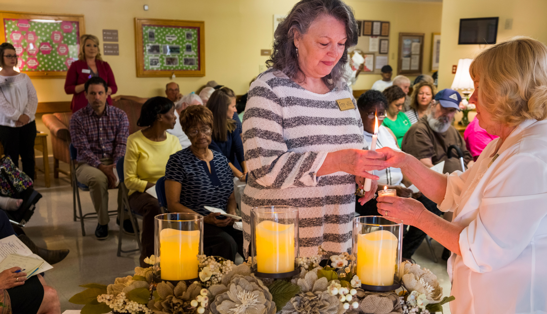 Mujer encendiendo una vela en un funeral