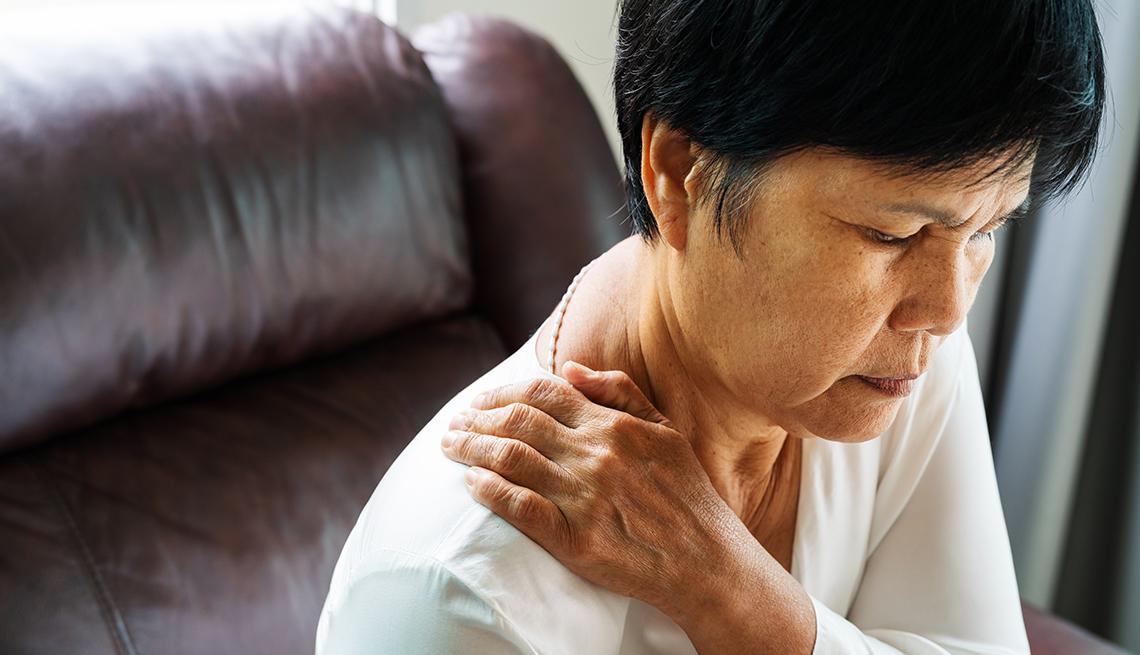 Mujer con su mano cerca del cuello en señal de dolor