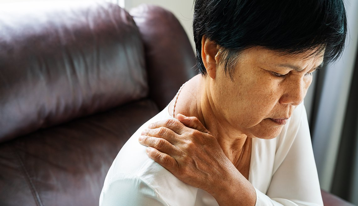 Mature Asian American woman suffering from neck pain.