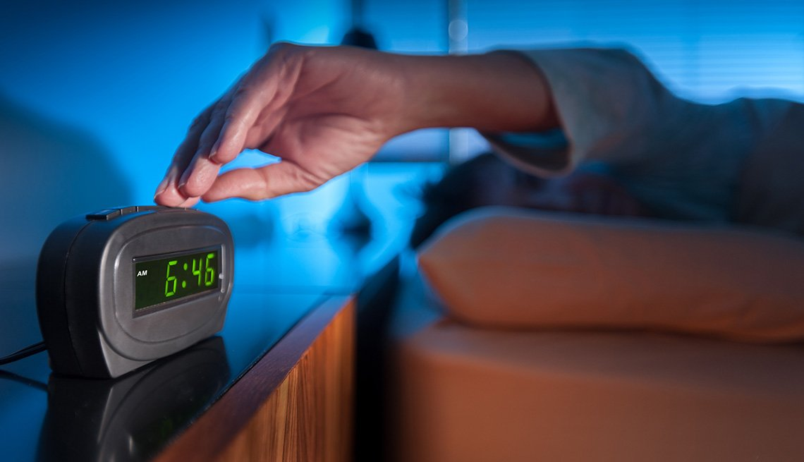 Woman pressing snooze button on early morning digital alarm clock.