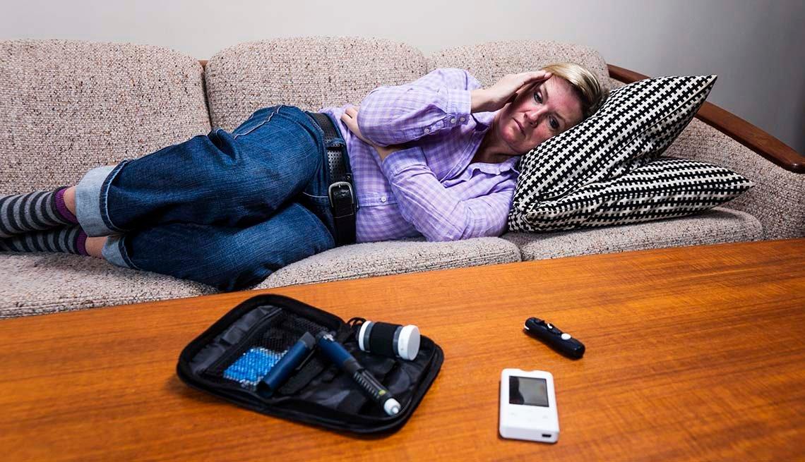 Mujer acostada en un sofá y un glucómetro sobre una mesa