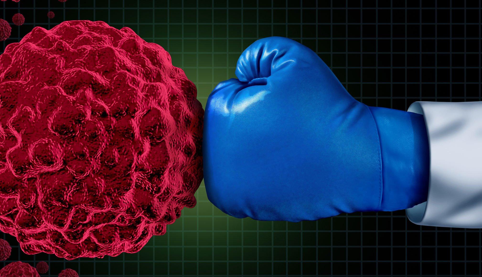 Mano con guante de boxeo golpeando al cáncer