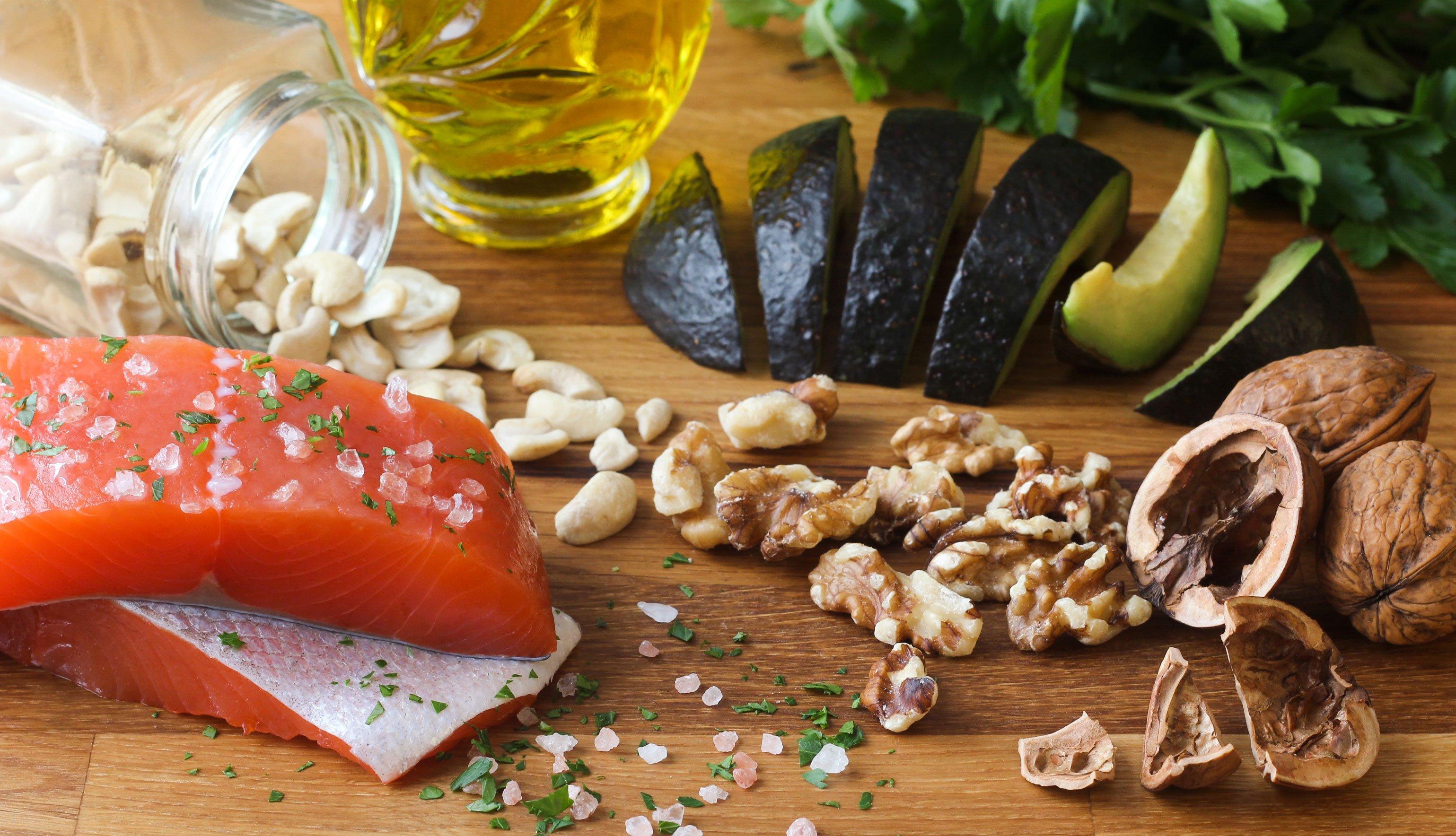 Salmón, nueces, aceite de oliva y aguacate sobre una mesa