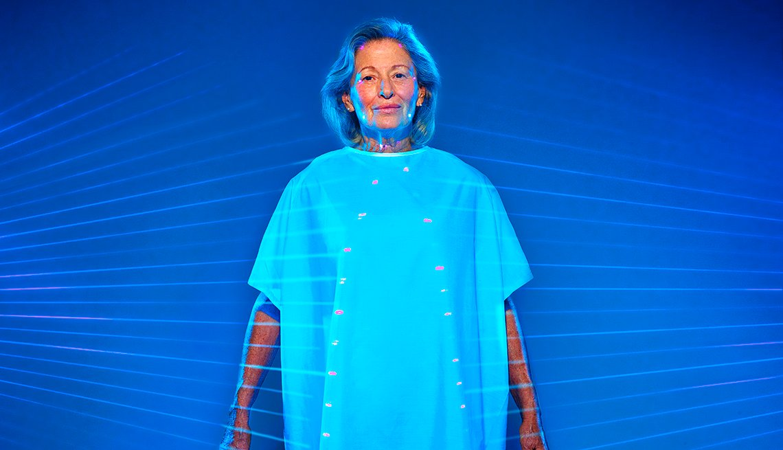 Mature woman wearing hospital gown with lines pointing to various parts of her body for medical testing.