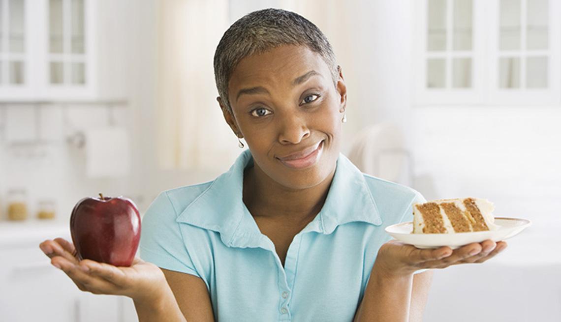 Mujer sostiene una manazana y un pedazo de pastel