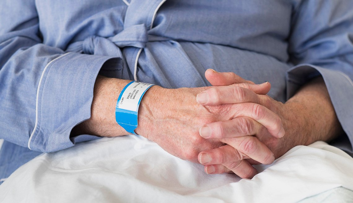 Mature man sitting in hospital bed, wearing a hospital wrist band.