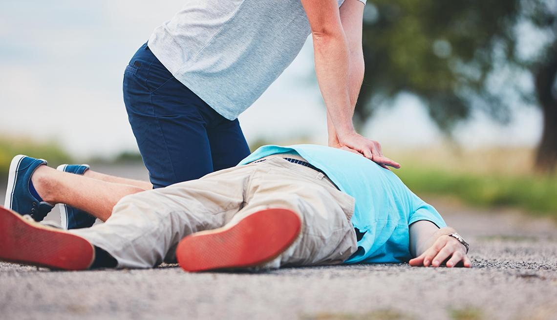 Hombre administra reanimación cardiopulmonar a otro hombre en el suelo