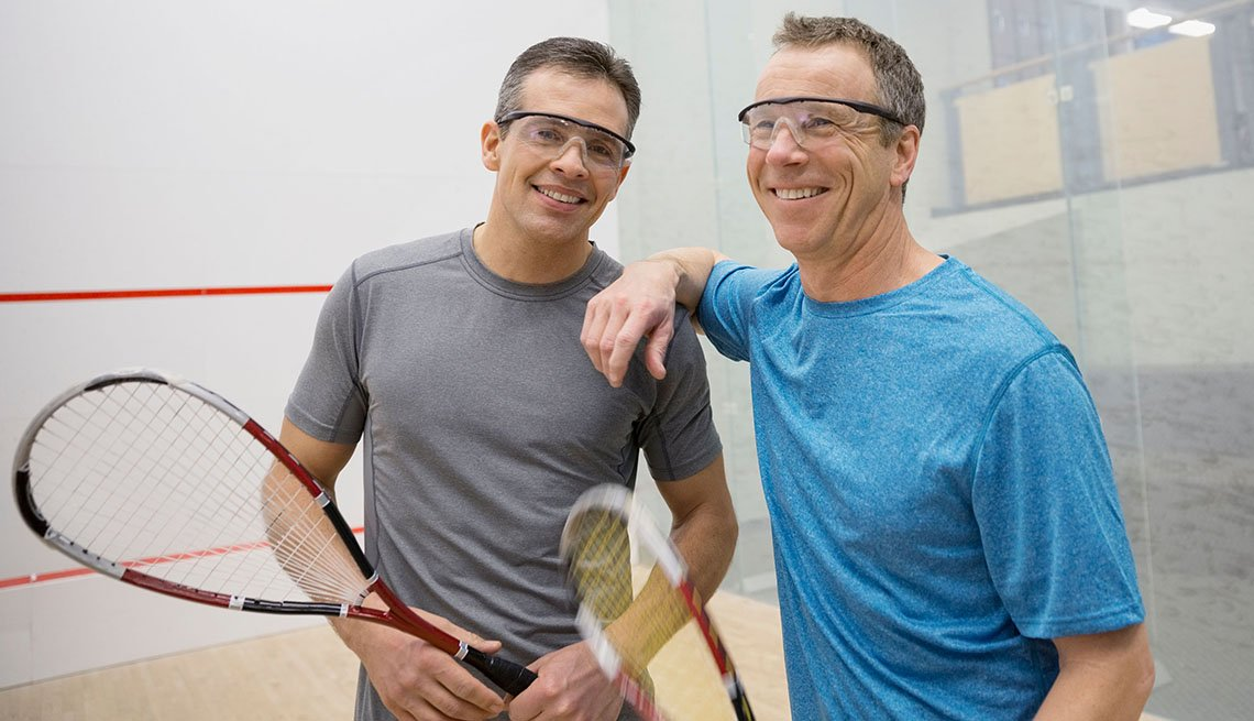 Portrait of smiling men holding squash rackets