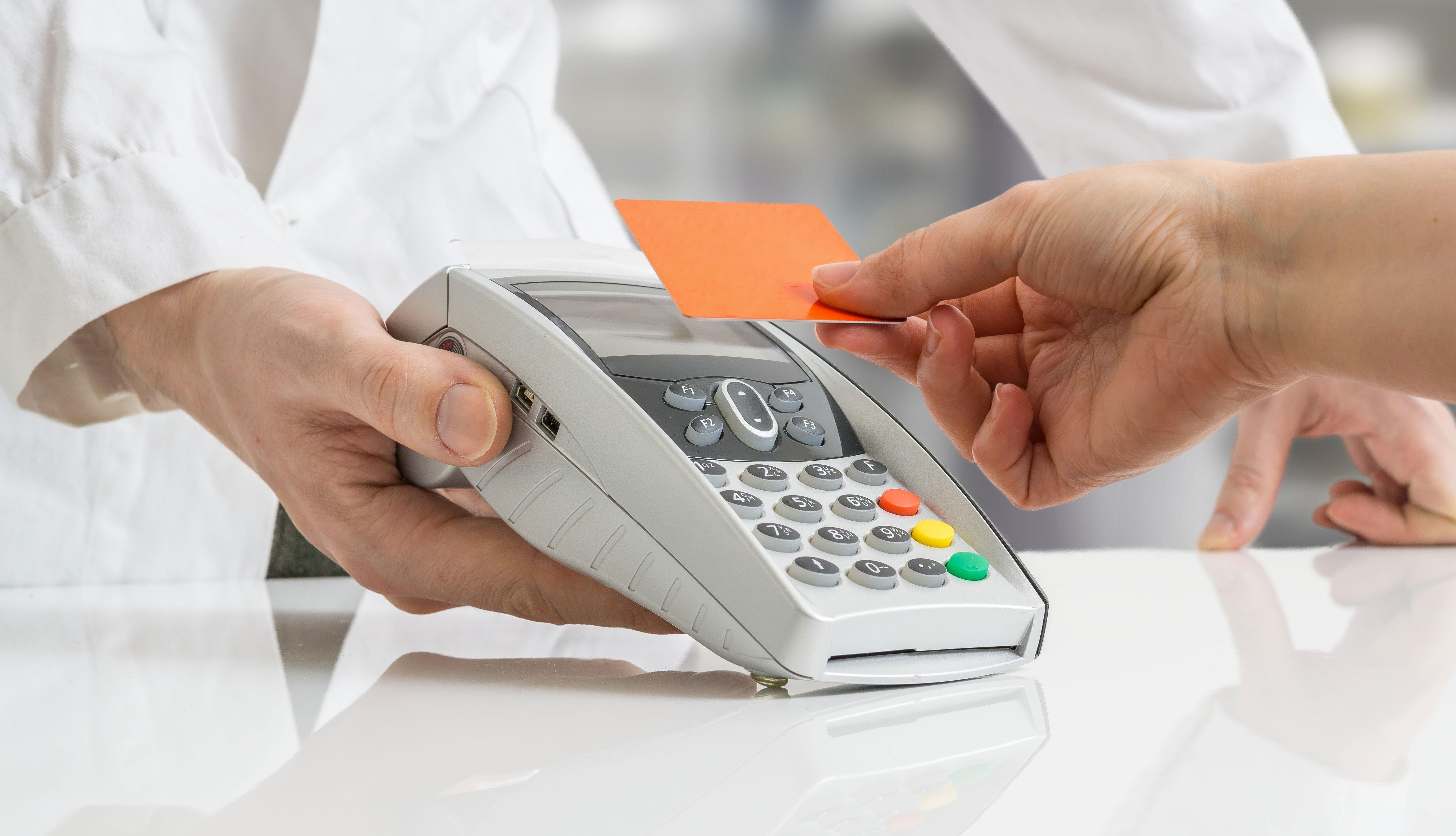 Cliente pagango con una tarjeta de descuentos