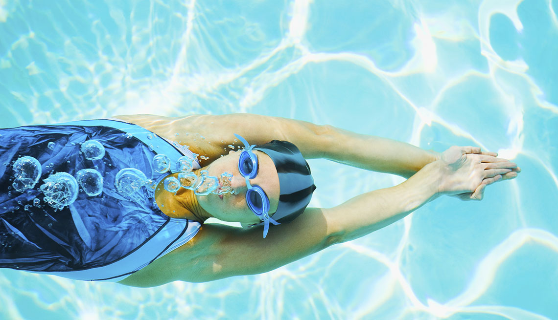 Woman swimming in pool with swim goggles