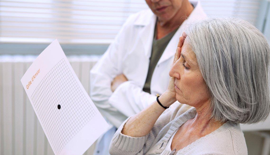 Mujer lee mientras se cubre un ojo en un examen de la vista