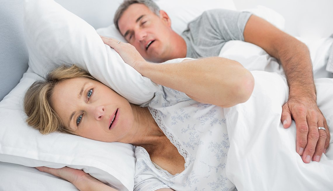 Couple asleep in bed with husband snoring