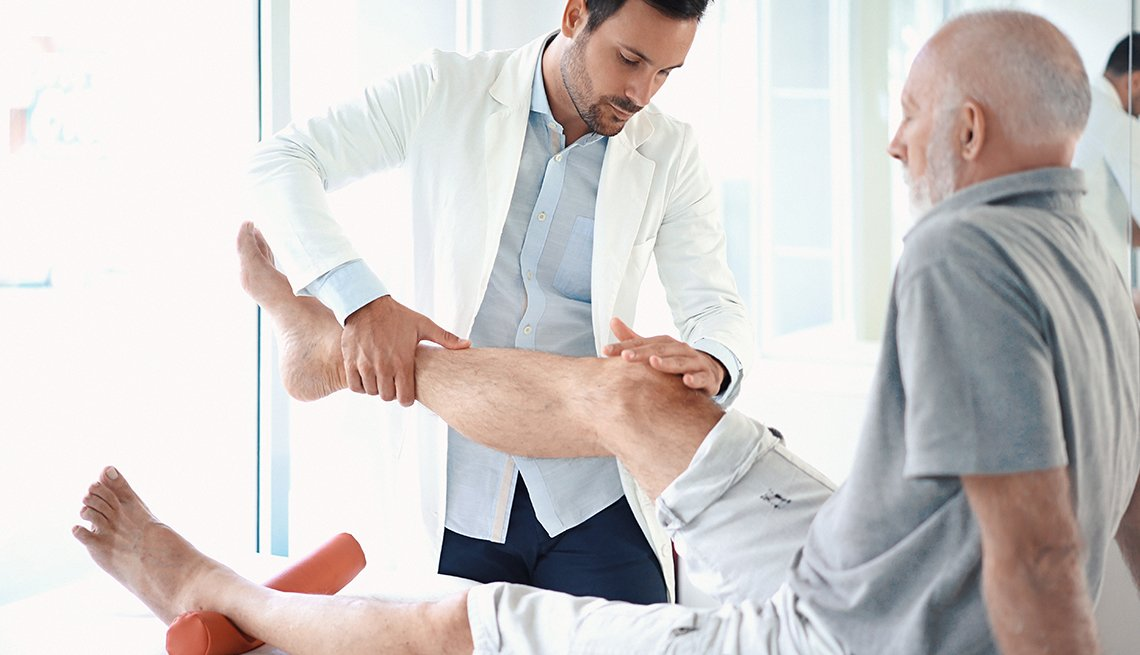 Doctor examining a man's knee