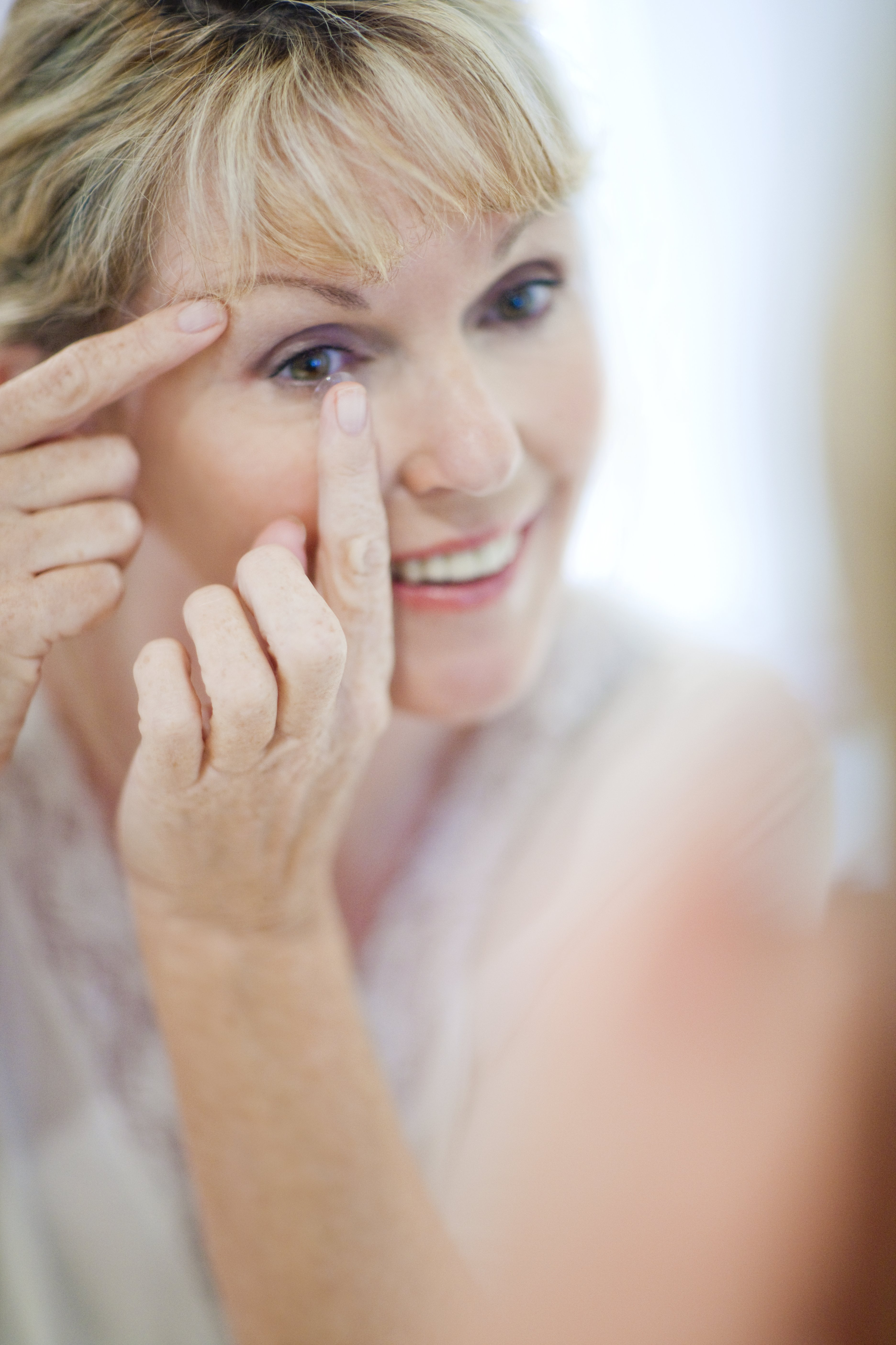 Senior woman looking at her reflection in the mirror while putting in contact lenses.