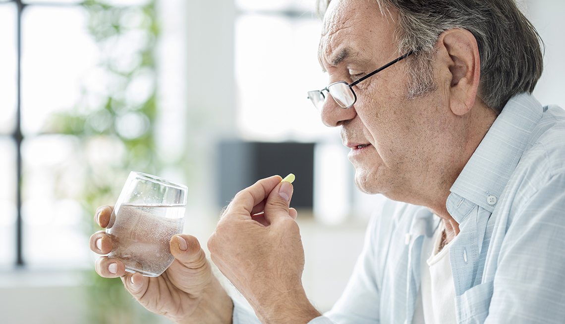 Older man taking a pill with a glass of water.